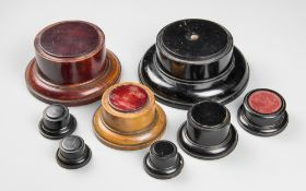 A 19TH CENTURY COLLECTION OF EIGHT WOODEN DISPLAY PLINTHS. Six with leather to the underside, the