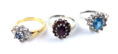 TWO VINTAGE SILVER AND GEM SET RINGS To include a garnet set daisy cluster ring and a blue and white