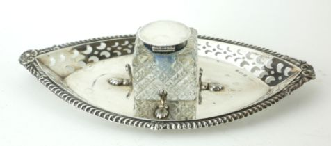 AN EDWARDIAN SILVER AND CUT GLASS OVAL INKWELL With pierced decoration and shell form supports,