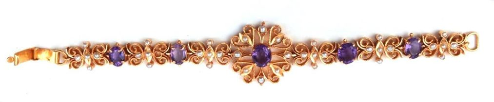 A 22CT GOLD, AMETHYST AND SEED PEARL BRACELET Having a central oval cut amethyst in a pierced frame,