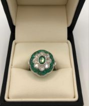 A 18CT WHITE GOLD, EMERALD AND DIAMOND CLUSTER RING With three diamonds to each shoulder (size N).