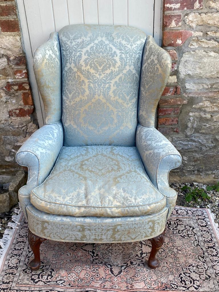 AN EARLY 20TH CENTURY WING ARMCHAIR Fashioned in the Georgian style, in blue floral fabric