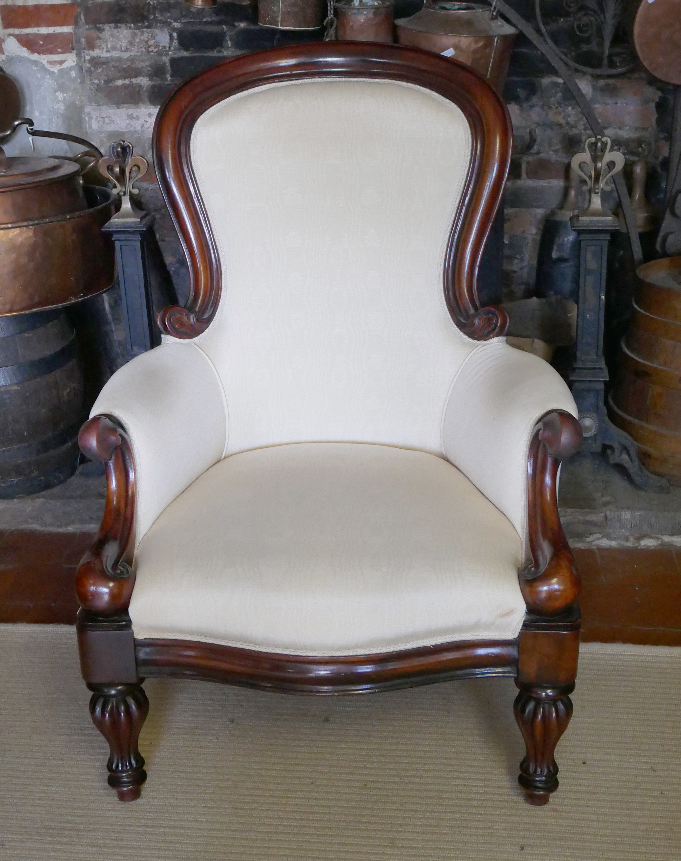 A VICTORIAN STYLE MAHOGANY SPOON BACK ARMCHAIR Upholstered in a cream water silk, raised on turned