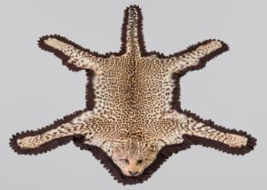 EDWARD GERRARD & SONS, AN EARLY 20TH CENTURY TAXIDERMY LEOPARD SKIN RUG WITH PARTIALLY MOUNTED