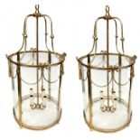 A PAIR OF BRASS LANTERNS IN THE REGENCY STYLE With four glass sections and rope twist swags above