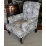 A 19TH CENTURY EASY ARMCHAIR In oatmeal floral fabric upholstery, raised on turned and fluted legs
