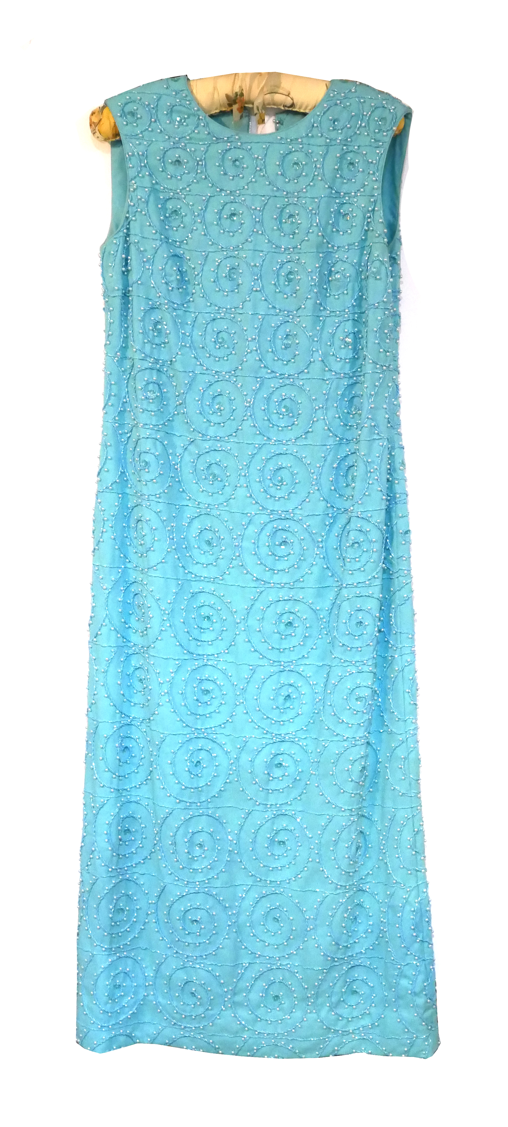 A VINTAGE TURQUOISE FABRIC LADIES' COCKTAIL DRESS Set with hand sewn beads and simulated pearls. (
