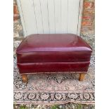 A OXBLOOD FAUX LEATHER UPHOLSTERED FOOTSTOOL With stud work, raised on square tapering legs. (68cm x