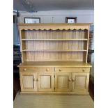 A VICTORIAN STYLE LIMED OAK DRESSER With open shelves above two long drawers and four cupboards,
