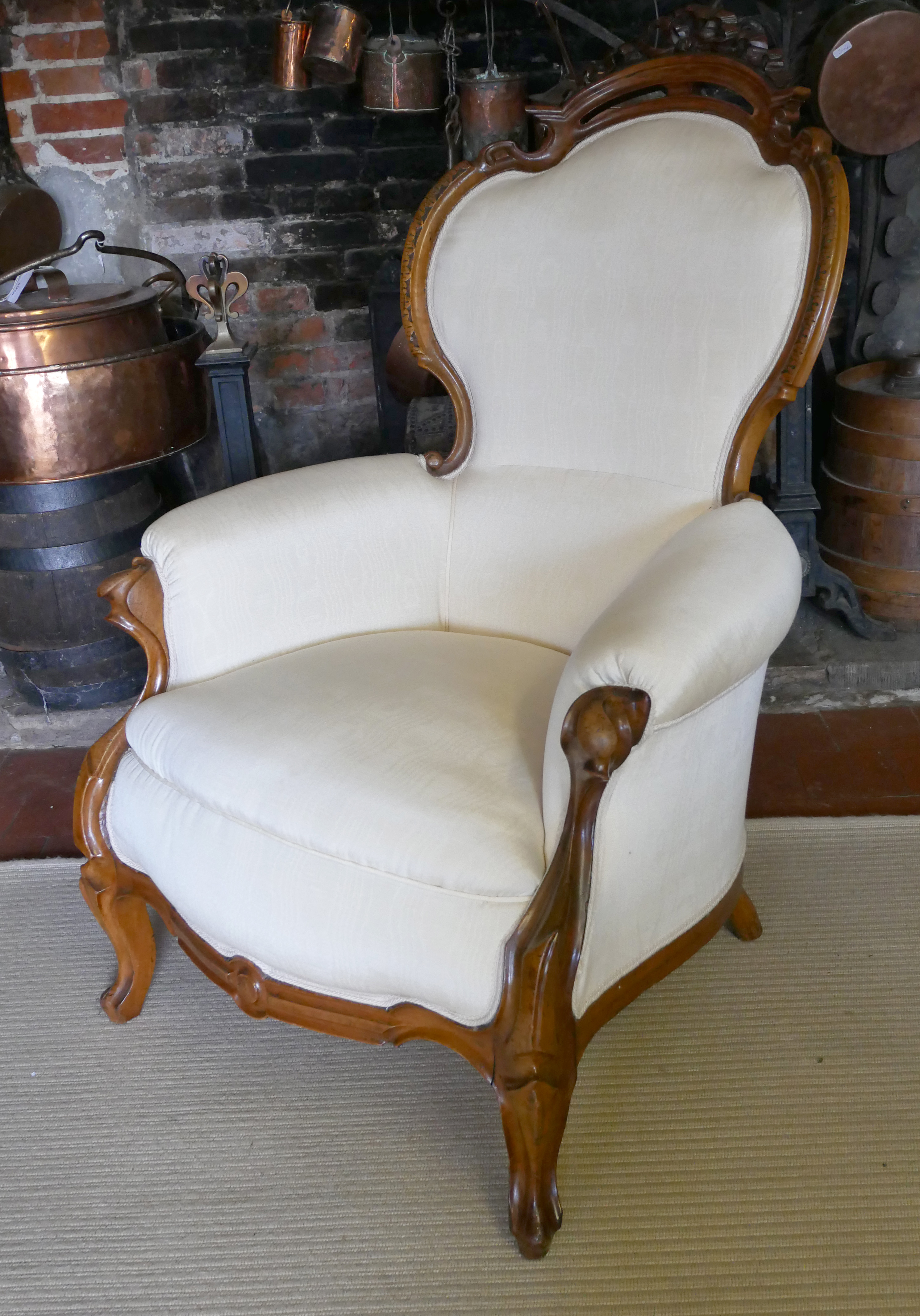 A 19TH CENTURY FRENCH ARMCHAIR Upholstered in a cream water silk, the mahogany frame with carved and
