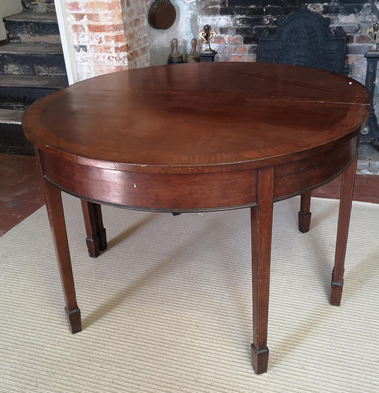 A 19TH CENTURY MAHOGANY AND CROSSBANDED 'D' END DINING TABLE With one extra leaf, raised on square