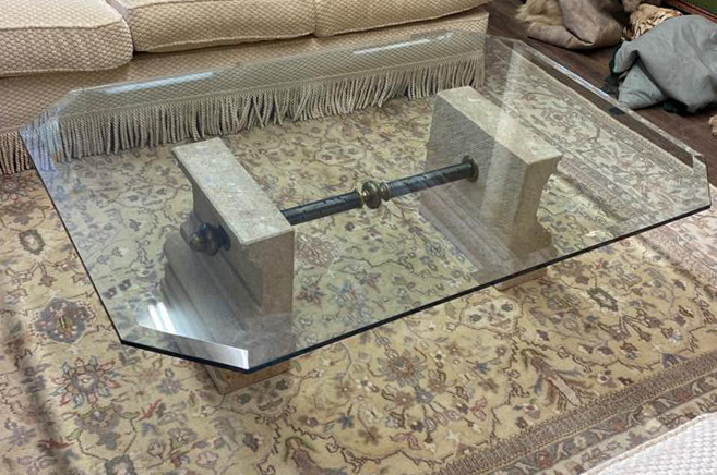 A 20TH CENTURY COFFEE TABLE With clear bevelled glass top supported on carved stone plinths,