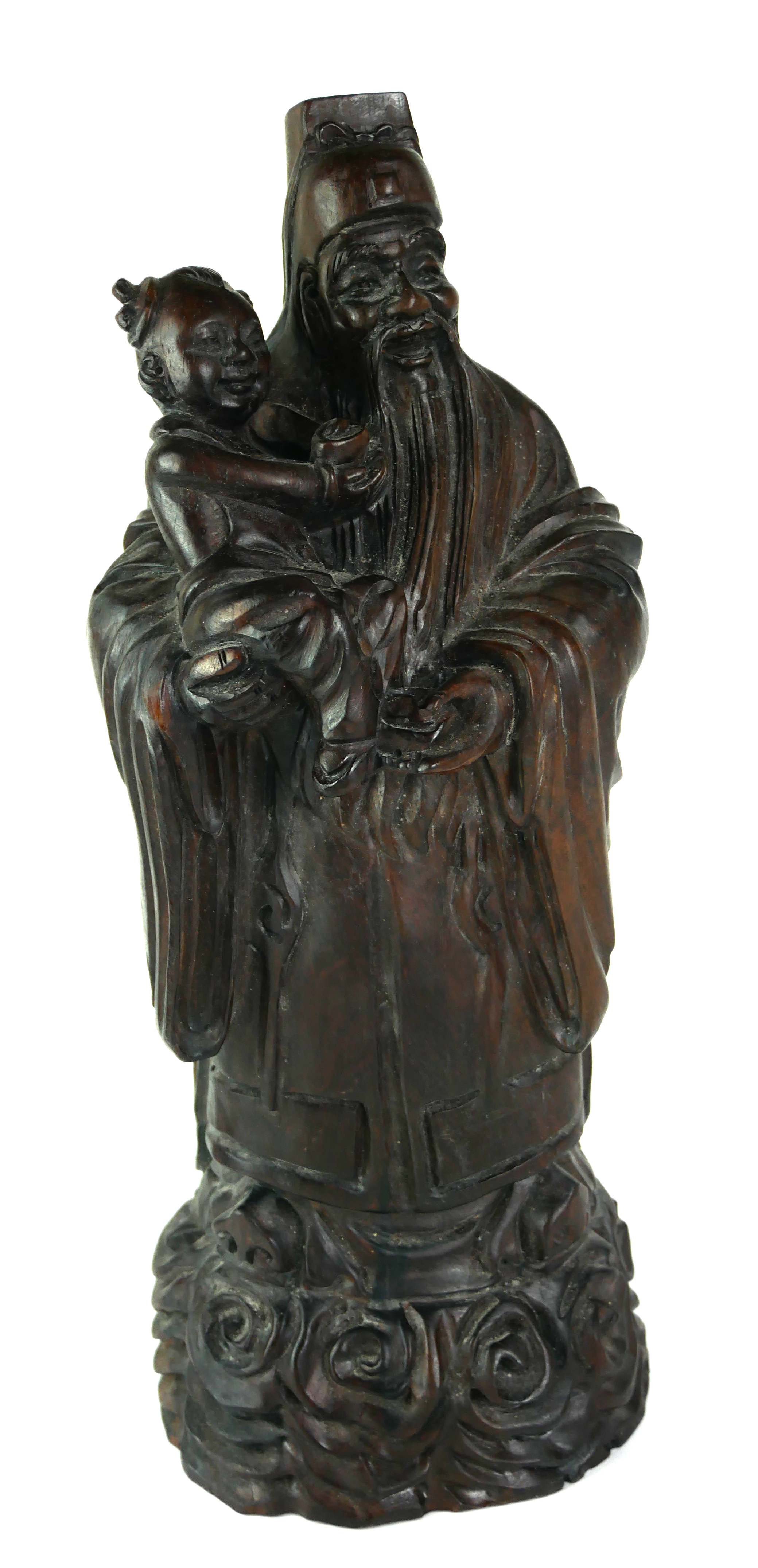 AN EARLY 20TH CENTURY CHINESE ROSEWOOD GROUP CARVING OF IMMORTAL FIGURE HOLDING A CHILD Raised on