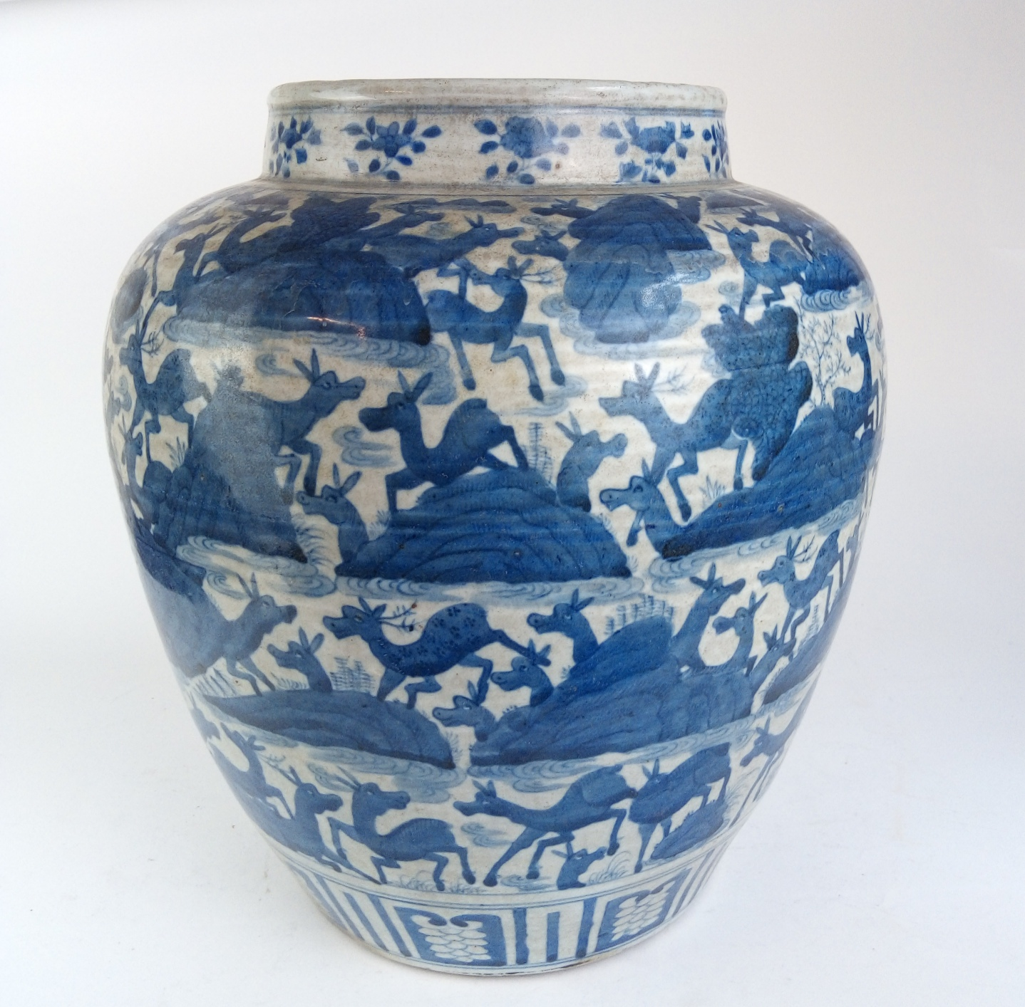 A LARGE CHINESE BLUE AND WHITE OVOID POTTERY VASE Decorated with multi deer with stylised rocks,