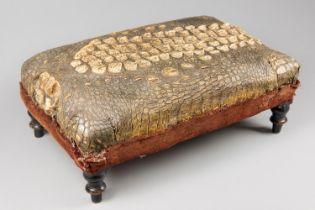 AN UNUSUAL LATE 19TH CENTURY TAXIDERMY CROCODILE SKIN FOOTSTOOL WITH EBONISED FEET AND VELVET