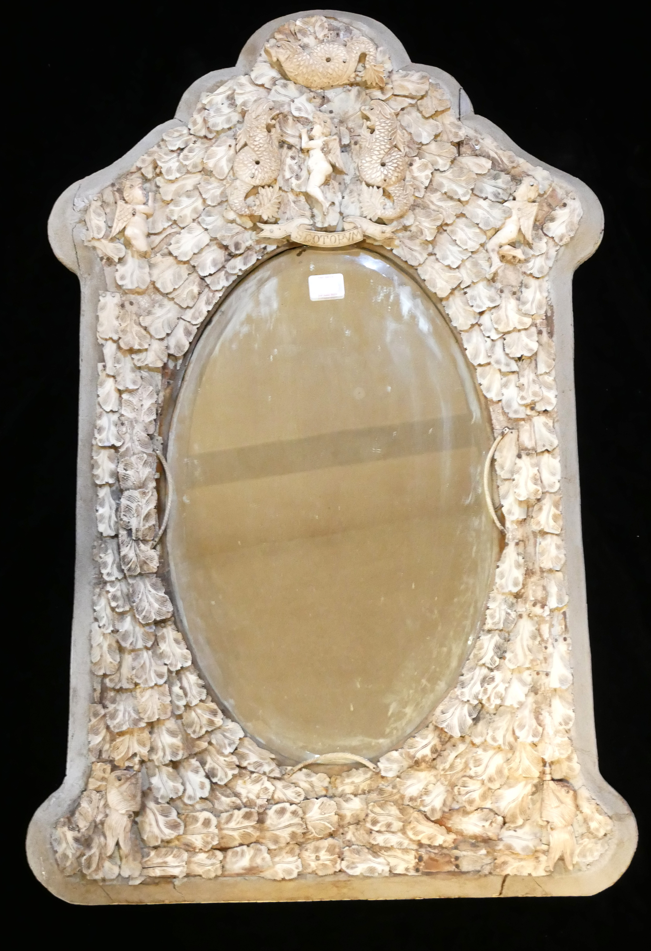 A 19TH CENTURY FRENCH IVORY FRAMED MIRROR Figured with a cherub flanked by dragons above an oval