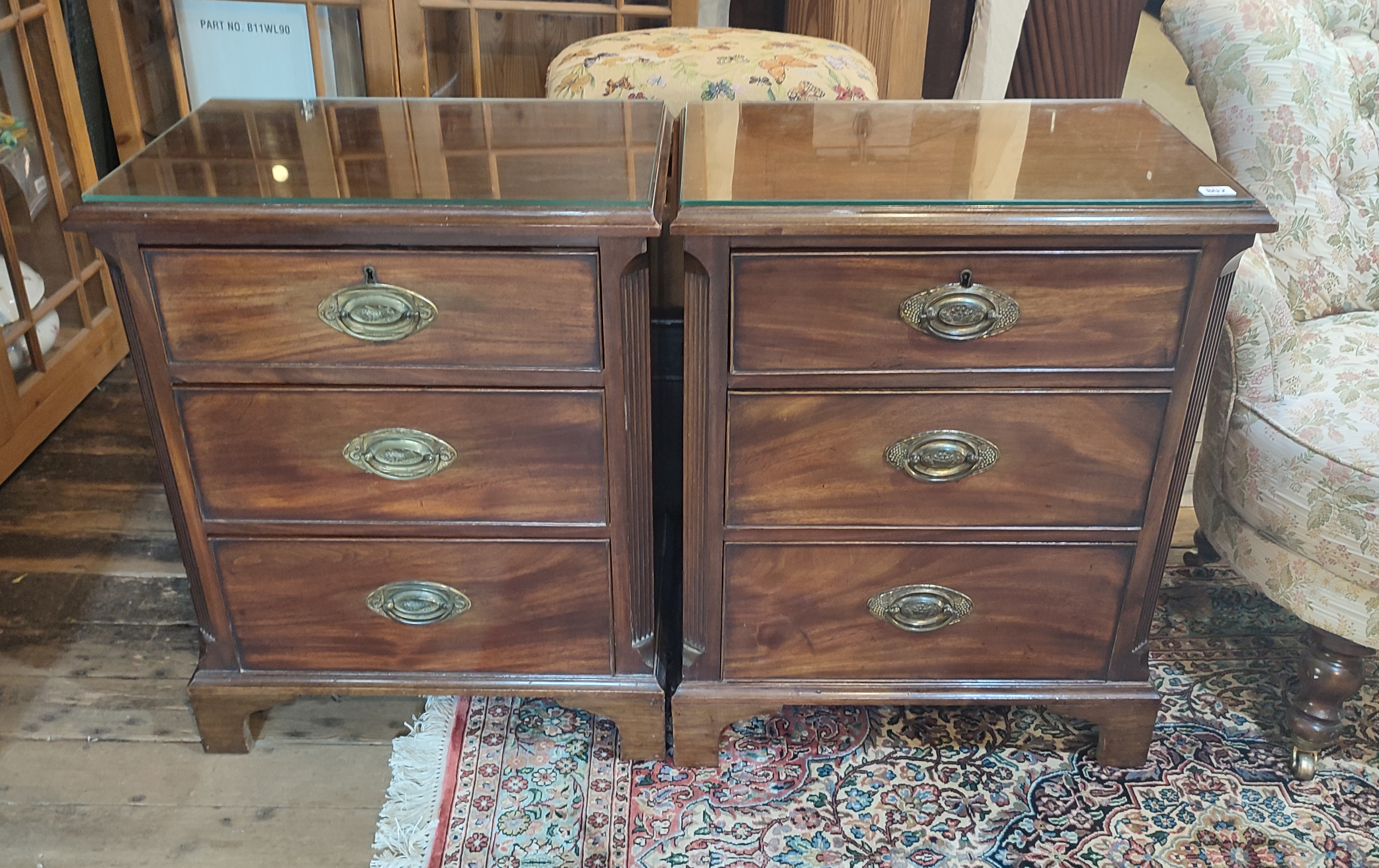A PAIR OF 19TH CENTURY MAHOGANY PEDESTAL CHESTS Three rolls fitted with brass furniture flanked by
