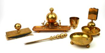AN ART DECO BRASS DESK SET Comprising an inkstand with spherical inkwell, matching letter knife,
