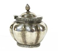 An oval, lobed, silver tea caddy