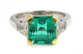 A platinum and gold Colombian emerald and diamond three stone ring,