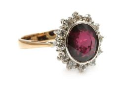 A gold ruby and diamond oval cluster ring,