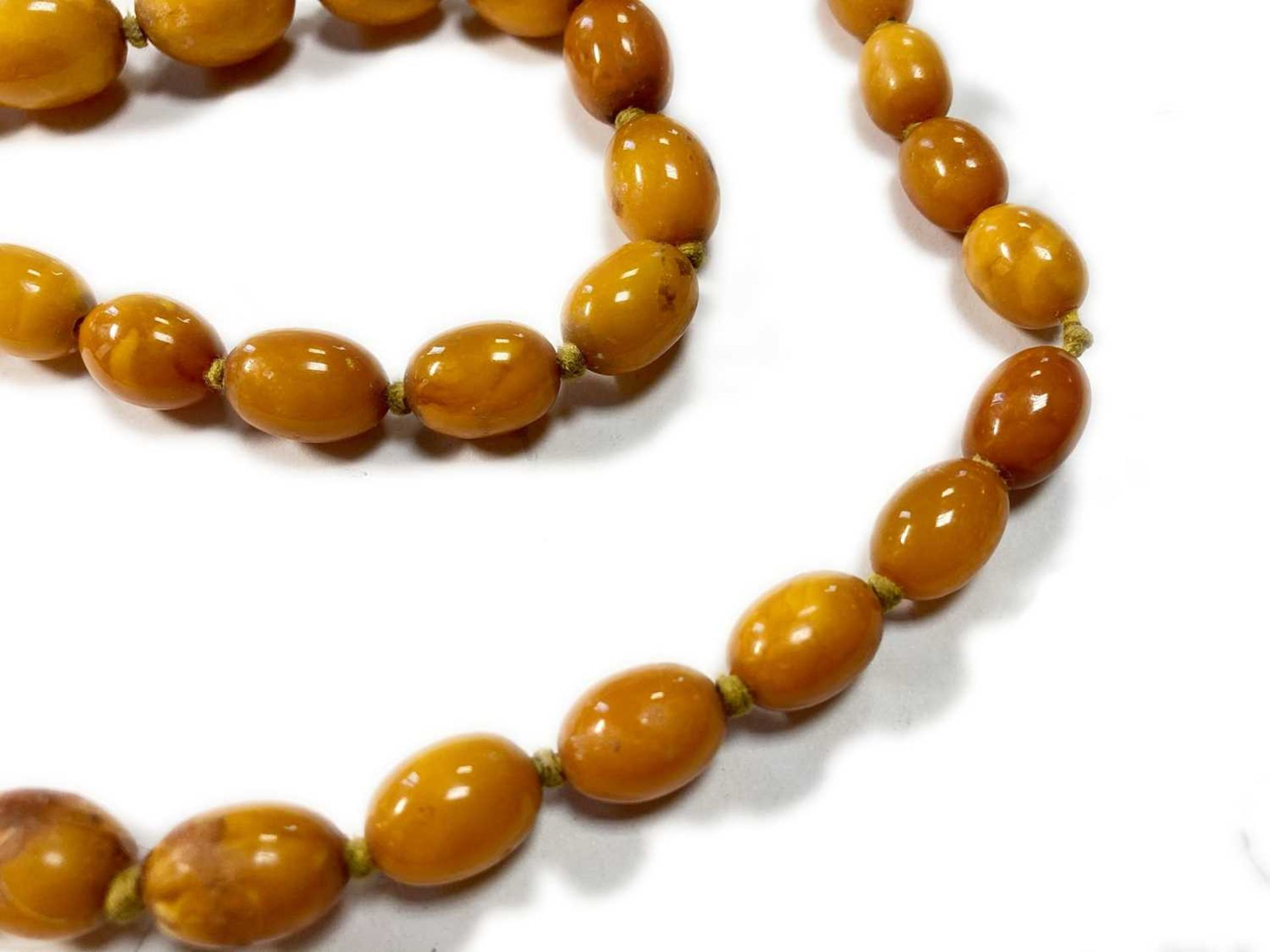 A single row graduated olive-shaped butterscotch amber bead necklace, - Image 8 of 12