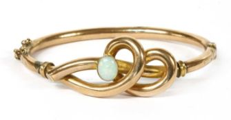 A gold opal set hollow hinged bangle,
