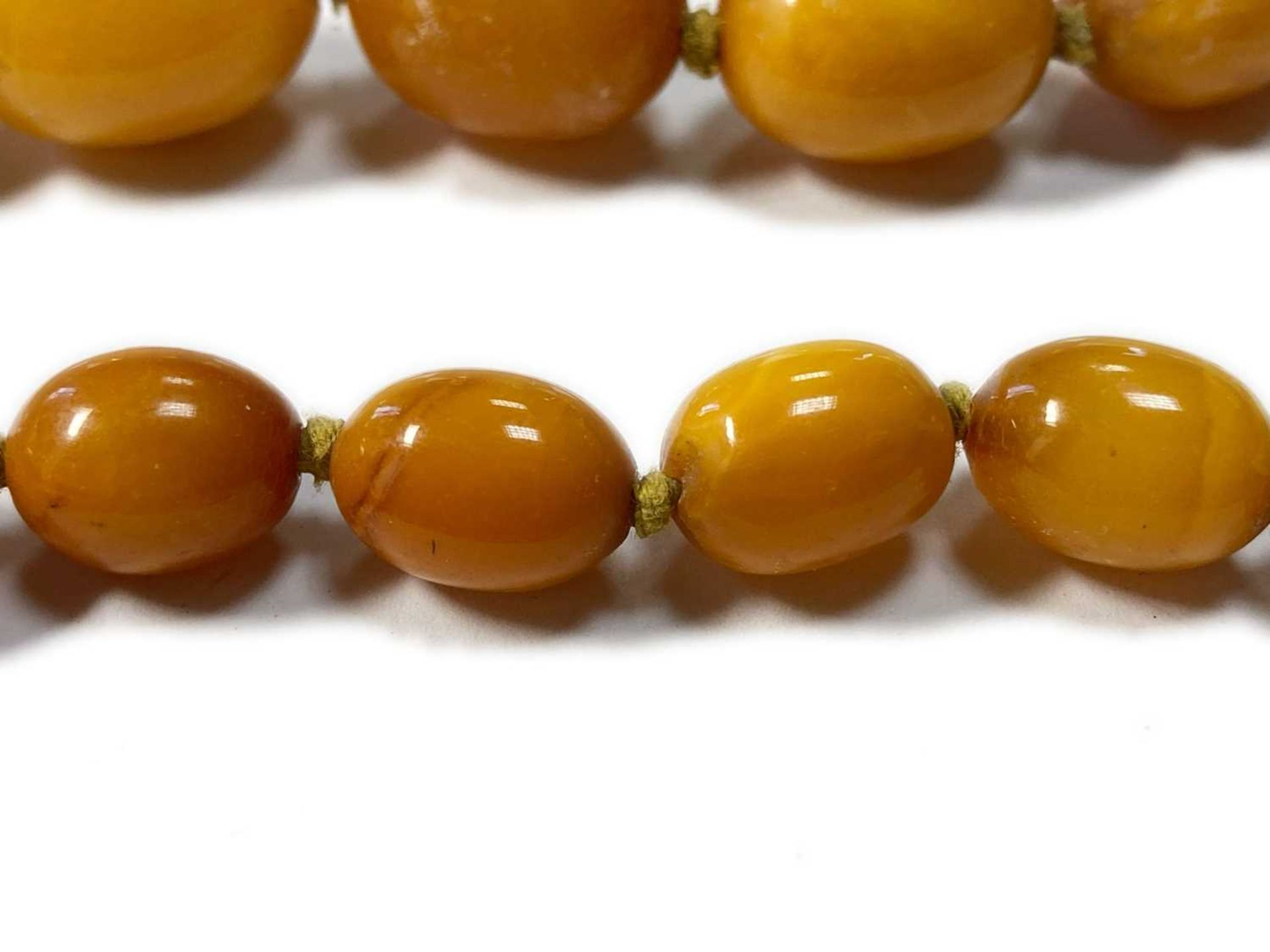 A single row graduated olive-shaped butterscotch amber bead necklace, - Image 3 of 12