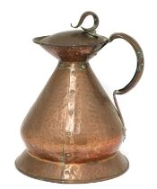 An Arts and Crafts hammered copper haystack measure and cover,