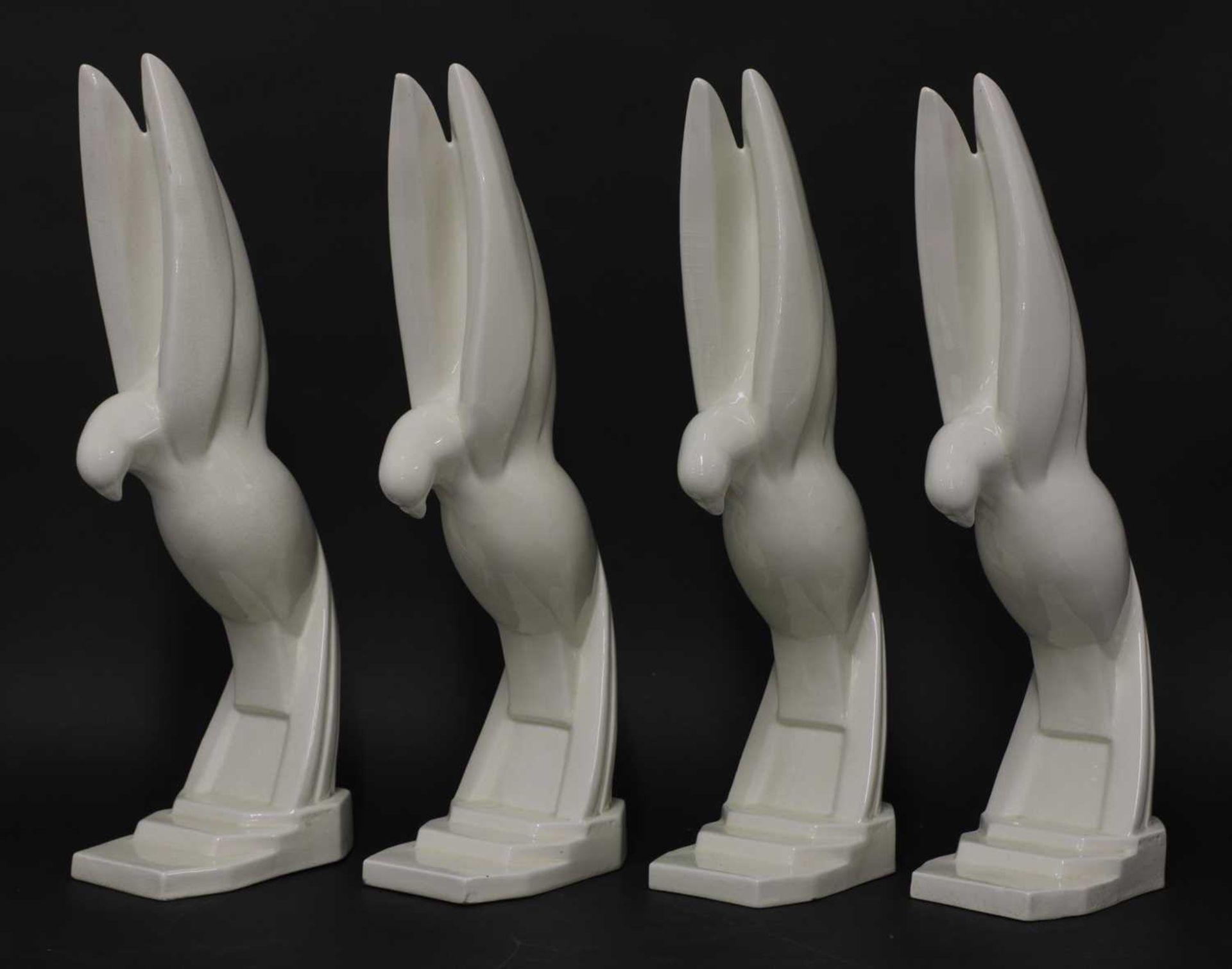 Four Art Deco moulded white glazed doves,