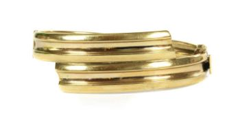 A 9ct gold oval hinged crossover bangle,