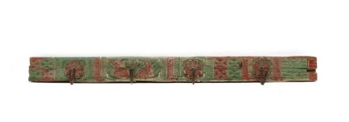 An Indian carved wood and polychrome decorated rack of four coat hooks,