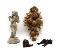 A carved and painted wooden figure of a cherub playing a flute,