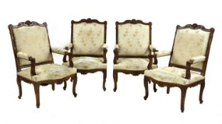 A set of four French Regency-style walnut elbow chairs,