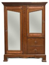 An Arts and Crafts oak mirrored wardrobe,