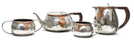 An Arts and Crafts pewter and copper mounted four-piece tea set,