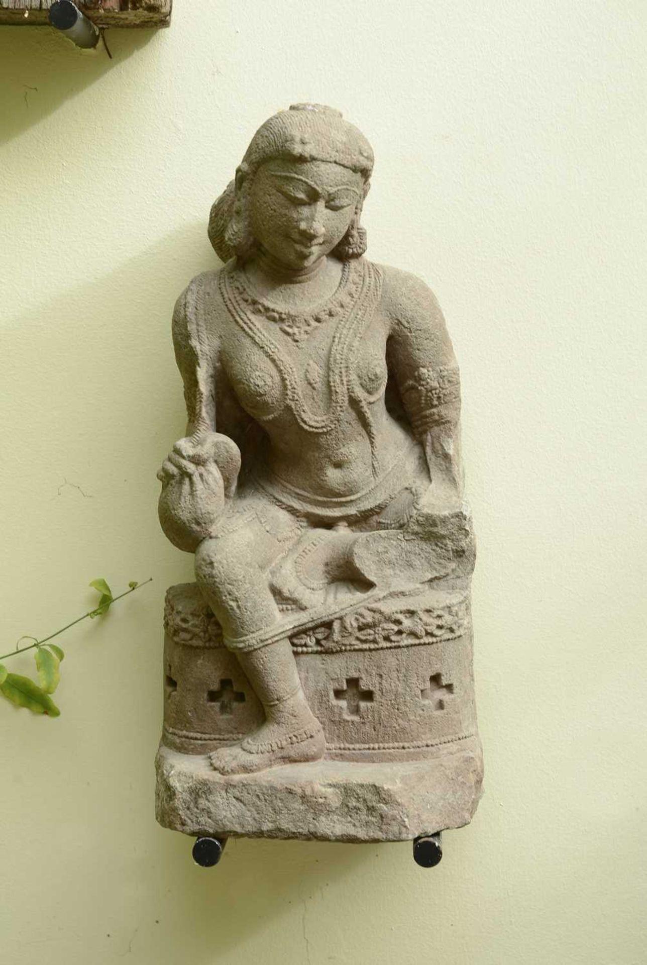 A carved sandstone figure of a dancer,