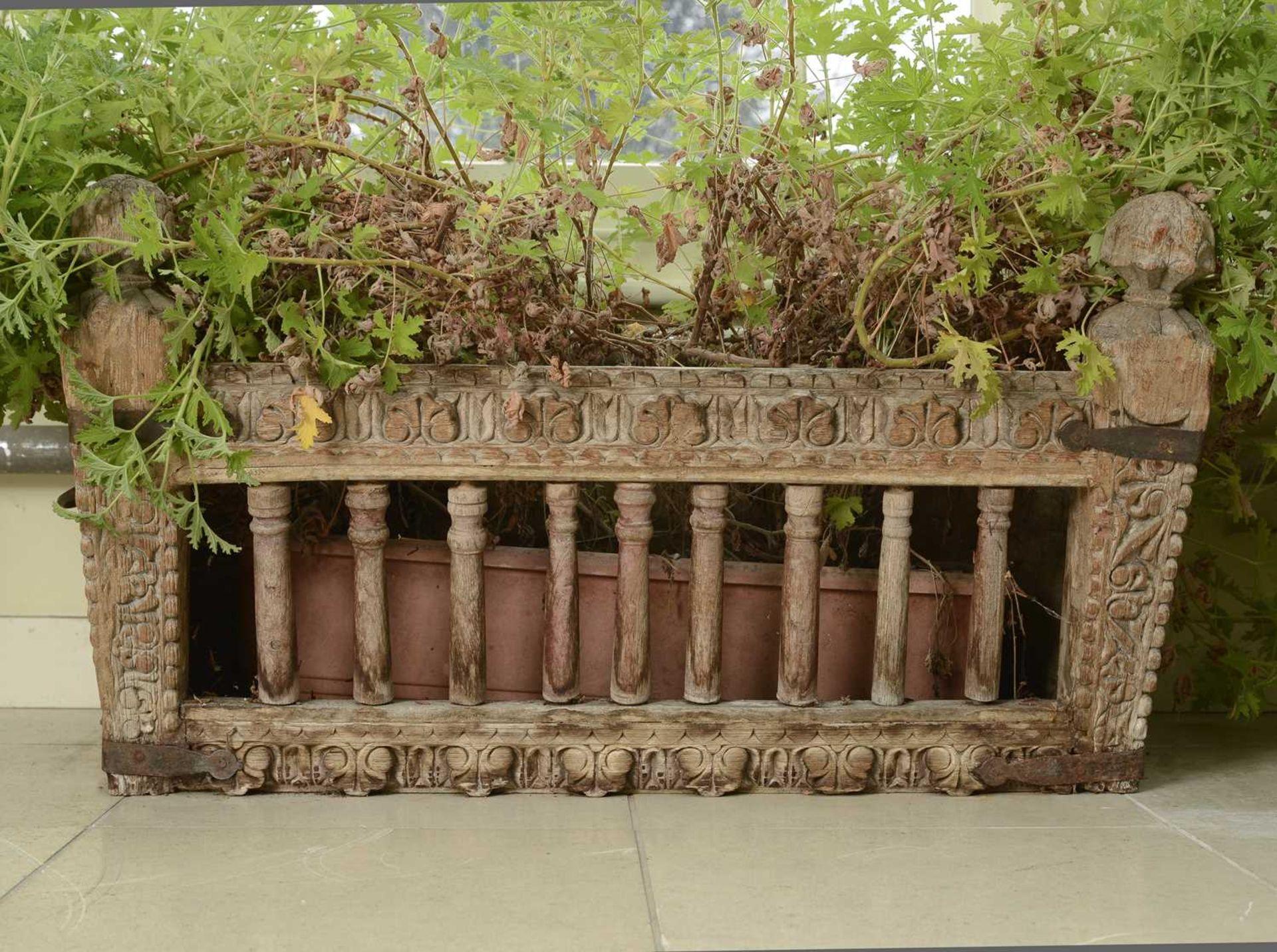 A carved hardwood manger/plant stand,