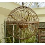 A large wrought iron gimballed light fitting,