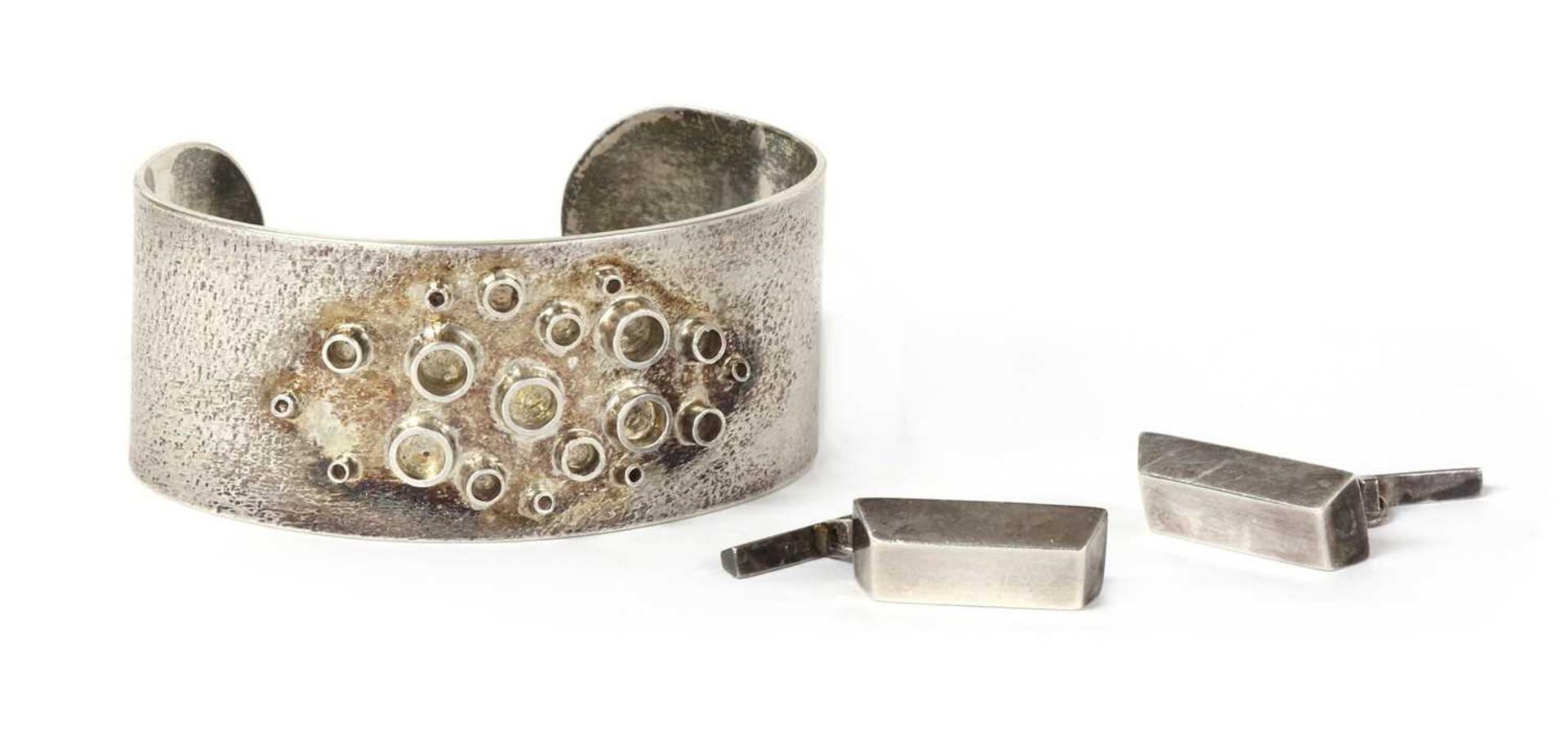 A handmade sterling silver torque bangle,