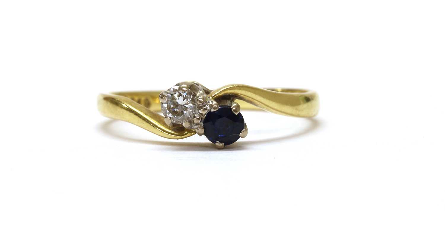 An 18ct gold two stone diamond and sapphire crossover ring,