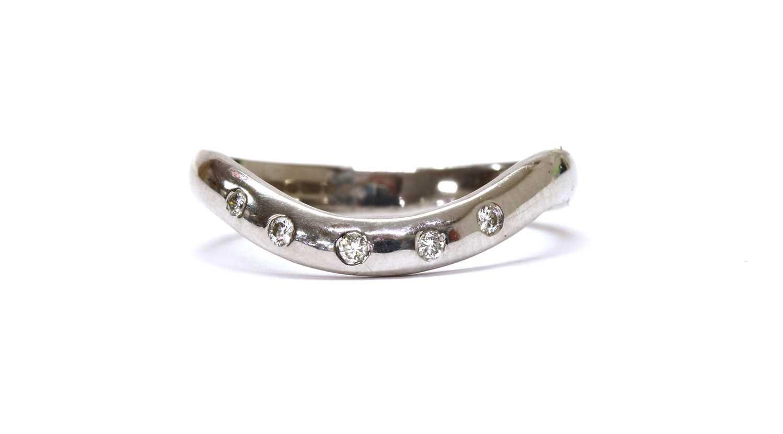 An 18ct white gold diamond set shaped band ring,