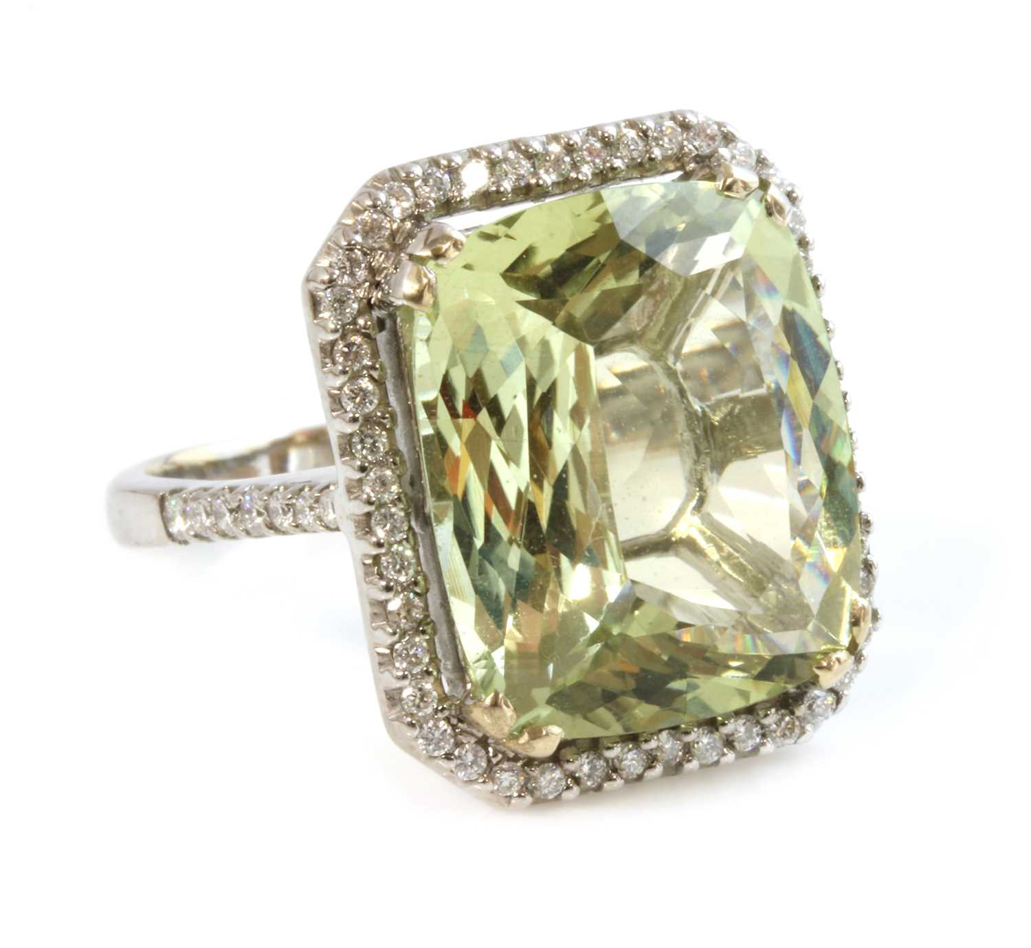 A white gold heliodor and diamond halo cluster ring,