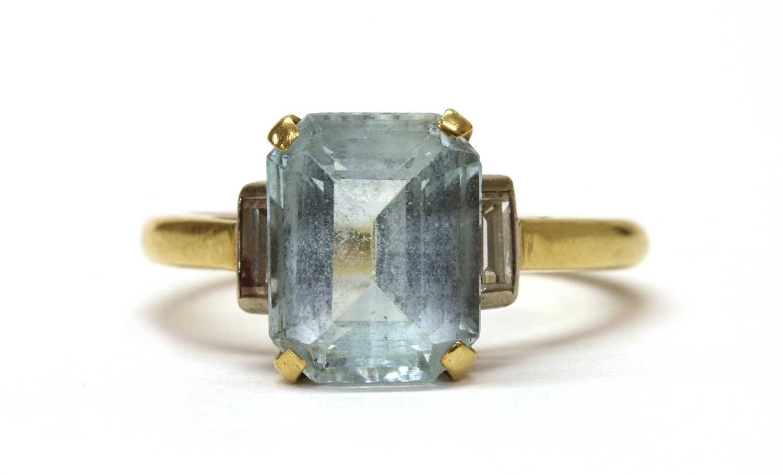 A gold blue topaz and diamond three stone ring,