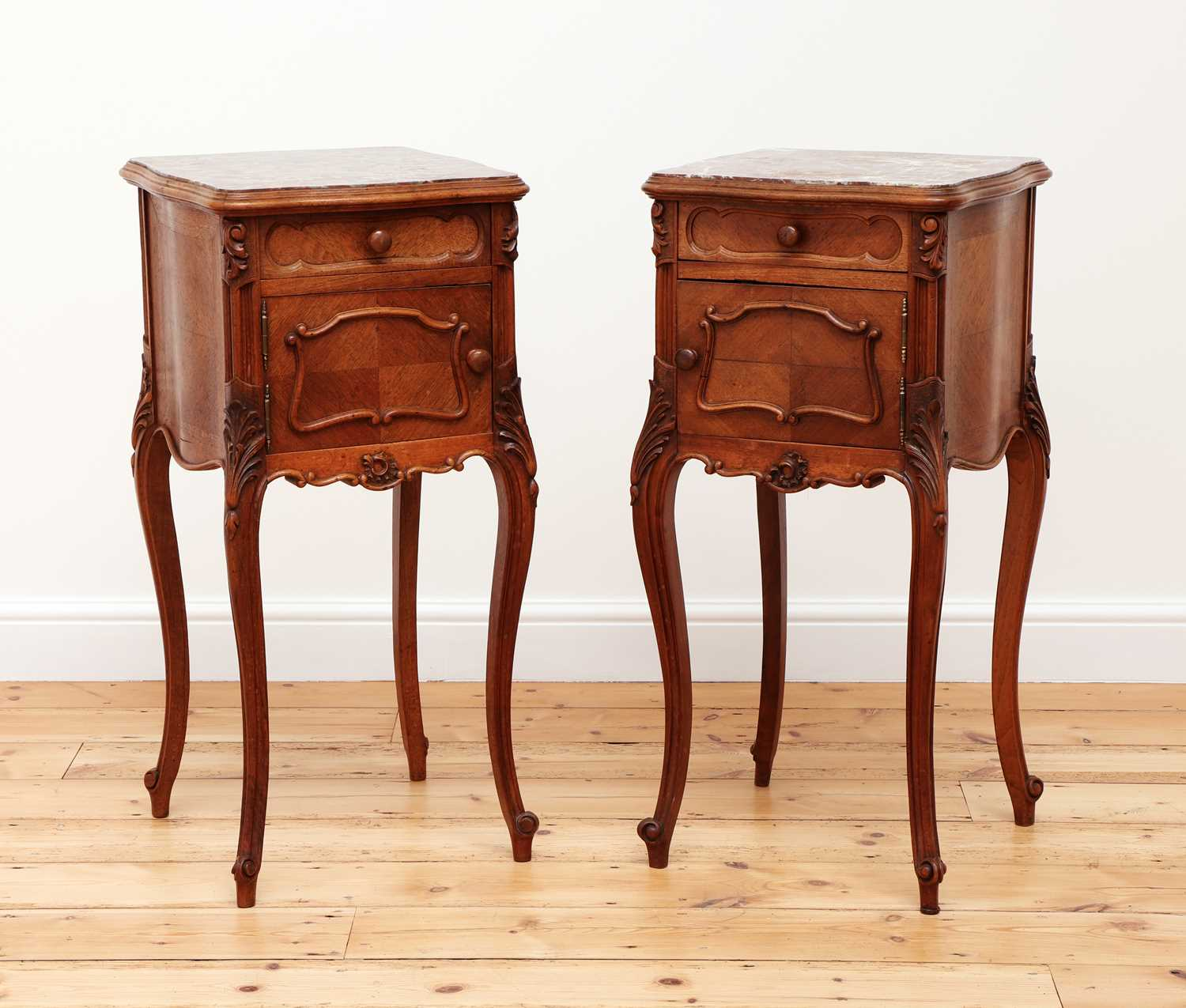 A pair of French Louis XV-style walnut bedside cabinets