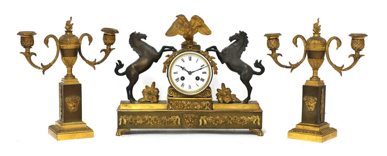 A French two-colour gilt-bronze three-piece clock garniture,