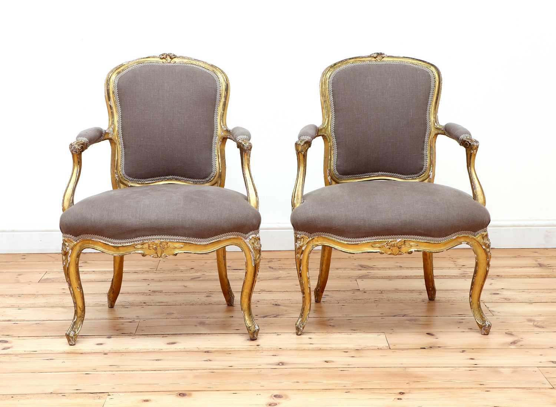 A pair of gilt-framed Louis XV-style armchairs,