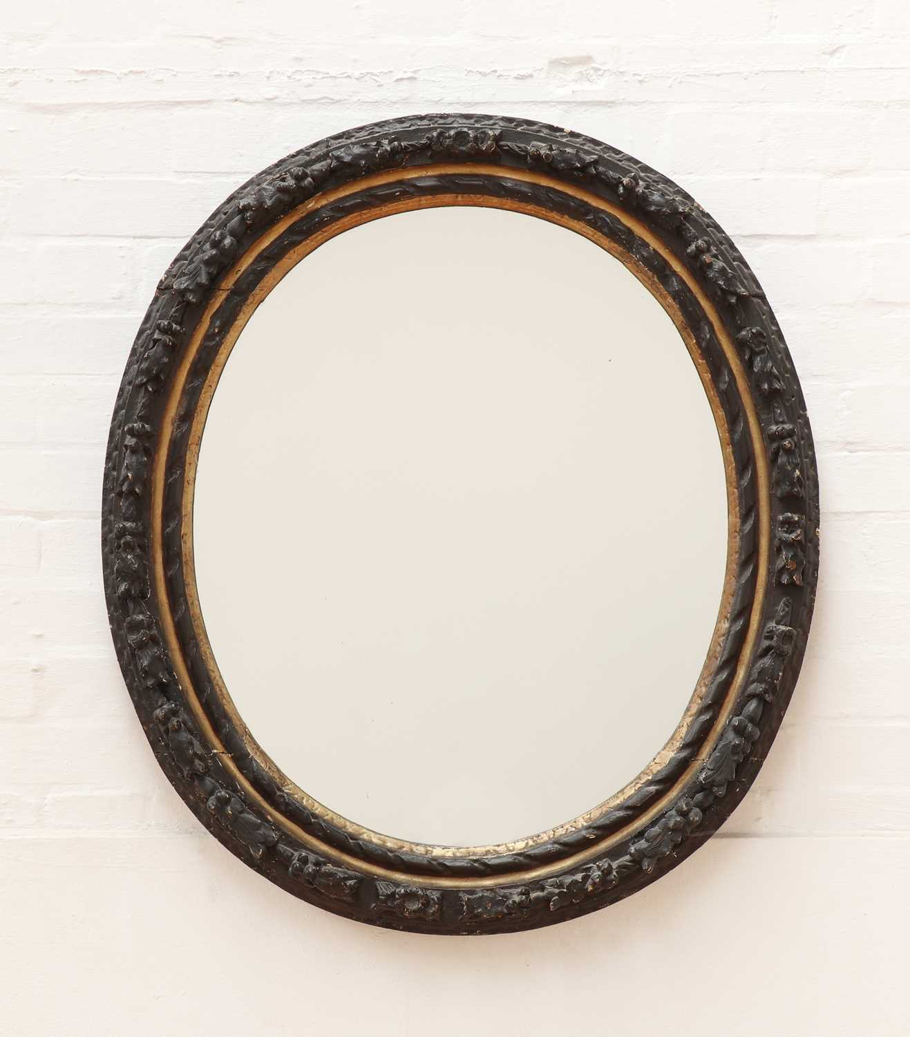 A carved giltwood and ebonised oval wall mirror,