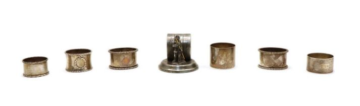 Six silver napkin rings and a figural silver plated example,