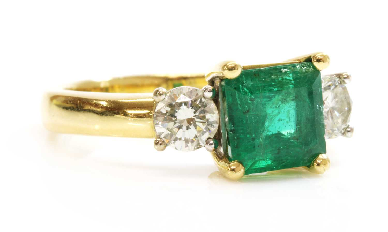 An 18ct two colour gold three stone emerald and diamond ring,